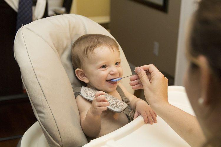 Ilustrasi bayi sedang makan MPASI atau makanan pendamping ASI.