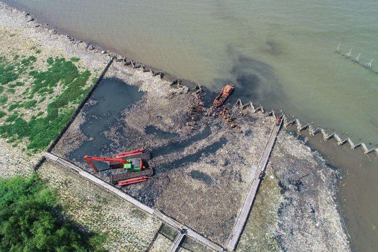 Petugas membersihkan lautan sampah yang menumpuk di kawasan Teluk Jakarta, Muara Angke, Jakarta Utara, Minggu (18/3/2018). Pencemaran limbah domestik rumah tangga di Teluk Jakarta ini memenuhi perairan seluas 7.500 meter persegi.