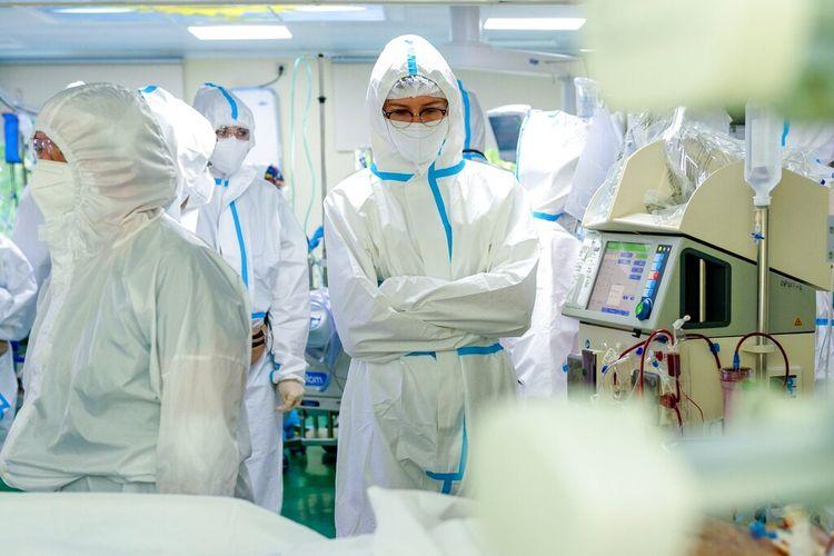 Petugas medis yang mengenakan pakaian khusus untuk melindungi diri dari virus corona berdiri di samping seorang pasien virus corona di Rumah Sakit Kota No. 52 untuk pasien virus corona di Moskow, Rusia, Kamis, 17 Juni 2021.