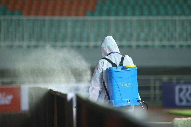 Seorang petugas kebersihan melakukan desinfeksi di sela-sela laga Liga 1 2021 Persipura Jayapura vs Persita Tangerang di Stadion Pakansari, Sabtu (28/8/2021).