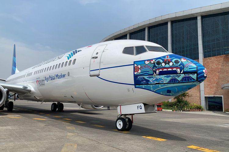 Pesawat Garuda Indonesia yang dipakaikan masker di bagian depannya.