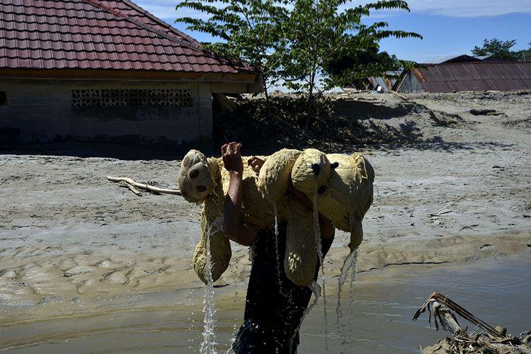 Warga mengangkat boneka di sekitar lokasi banjir bandang Masamba, Kabupaten Luwu Utara, Sulawesi Selatan, Jumat (17/7/2020). Hingga hari ini, jumlah korban meninggal mencapai 32 orang sementara puluhan lainnya masih dalam pencarian.