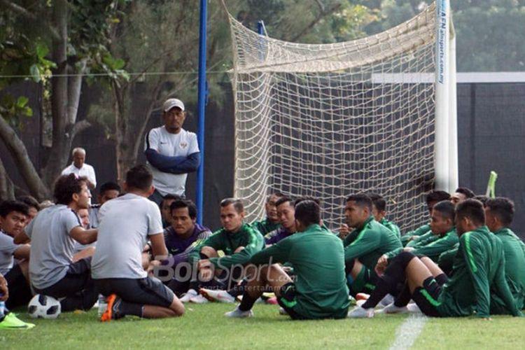 Pelatih timnas U-23 Indonesia, Luis Milla (ketiga dari kiri/menduduki bola), berbicara kepada para pemain sebelum memulai sesi latihan di Lapangan ABC, Senayan, Jakarta, Kamis (16/8/2018).