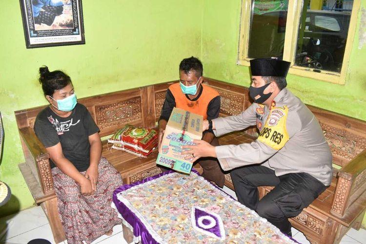 Kapolres Pasuruan Kota, AKBP Dony Alexander saat memberikan bantuan sembako kepada tukang becak yang ketahuan mencuri beras.