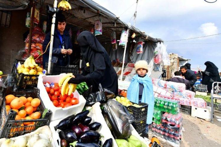 Pengungsi membeli sayuran dan buah-buahan di pasar kamp pengungsian Al-Hol, Suriah, yang saat ini dipenuhi dengan lebih dari 70.000 orang. (AFP/CACACE GIUSEPPE)