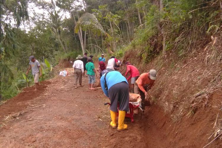 Warga Dusun Cilimus, Desa Indragiri, Kecamatan Panawangan, Kabupaten Ciamis, bergotong-royong menutup retakan tanah di sebuah bukit.