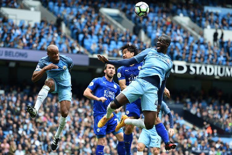 Striker Leicester City, Shinji Okazaki, mencoba memenangi duel udara menghadapi dua pemain Manchester City, Vincent Kompany dan Yaya Toure, dalam pertandingan Premier League di Stadion Etihad, Sabtu (13/5/2017).