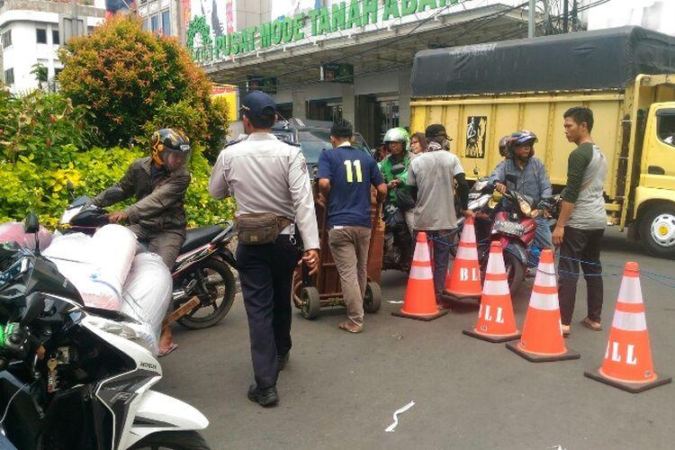 Porter di Pasar Tanah Abang masih nekat menerobos traffic cone yang digunakan untuk menutup akses berputar kendaraan di depan Blok A, Rabu (10/1/2018).