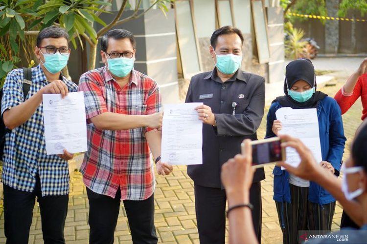 Direktur RSUD dr Iskak Tulungagung dr Supriyanto Dharmoredjo, Sp.B, M.Kes. (kedua kanan) dan tiga dari total empat tenaga medis yang dinyatakan sembuh COVID-19 menunjukkan surat keterangan sehat pada hari pertama kebebasan mereka keluar dari rumah karantina di Asrama RSUD dr  Iskak KabupatenTulungagung, Jawa Timur, Rabu (22/4/2020). ANTARA/Destyan Sujarwoko