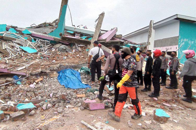 Petugas mengamati bangunan RS Mitra Manakarra yang roboh pascagempa bumi, di Mamuju, Sulawesi Barat, Jumat (15/1/2021). Petugas BPBD Sulawesi Barat masih mendata jumlah kerusakan dan korban akibat gempa bumi berkekuatan magnitudo 6,2 tersebut.