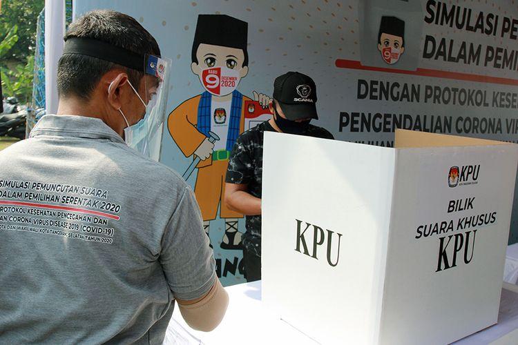 Petugas Kelompok Penyelenggara Pemungutan Suara (KPPS) dengan menggunakan alat pelindung diri (APD) mengawasi pemilih di bilik suara khusus saat simulasi pemungutan suara dengan protokol kesehatan pencegahan dan pengendalian COVID-19 di TPS 18 Cilenggang, Serpong, Tangerang Selatan, Banten, Sabtu (12/9/2020). KPU akan menyiapkan satu bilik suara khusus di setiap TPS yang diperuntukan bagi pemilih yang suhu tubuhnya diatas 37 derajat saat pemungutan suara Pilkada serentak 2020.