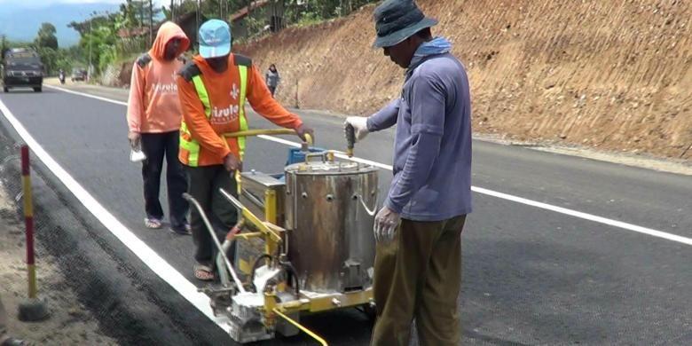 Sejumlah pekerja melakukan finishing yaitu membuat marka jalan di Tanjakan Ciregol, Tonjong, Brebes, Jawa Tengah sebelum dilintasi kendaraan.