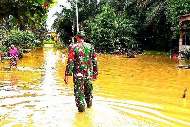 Babinsa Koramil 10/Kunto Darussalam, Koptu Yuliarman mengecek kondisi banjir yang melanda ratusan rumah warga di Desa Sontang, Kecamatan Bonai Darussalam, Kabupaten Rohul, Riau, Senin (23/11/2020).