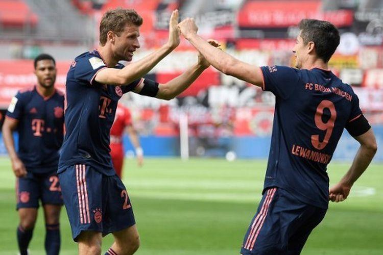 Thomas Mueller dan Robert Lewandowski merayakan gol Bayern Muenchen ke gawang Bayer Leverkusen pada lanjutan laga pekan ke-30 Bundesliga Jerman di Stadion BayArena, Sabtu (6/6/2020).