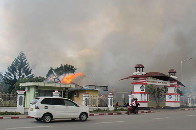 Pengendara melintasi Kantor Bupati Jayawijaya yang terbakar saat aksi unjuk rasa di Wamena, Jayawijaya, Papua, Senin (23/9/2019). ANTARA FOTO/Marius Wonyewun/wpa/foc.