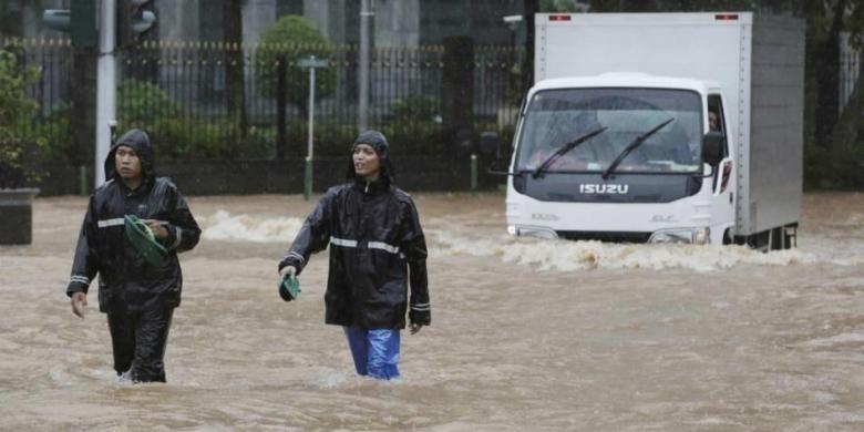 Warga melintasi banjir di Jakarta Pusat, Senin (9/2/2015). Curah hujan yang tinggi mengakibatkan sejumlah tempat di ibu kota terendam banjir.