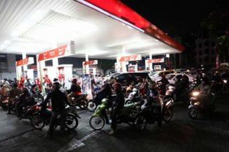 Warga antre mengisi bahan bakar minyak (BBM) di SPBU Cikini, Jakarta Pusat, seusai Presiden Joko Widodo mengumumkan kenaikan harga BBM, Senin (17/11/2014) malam.