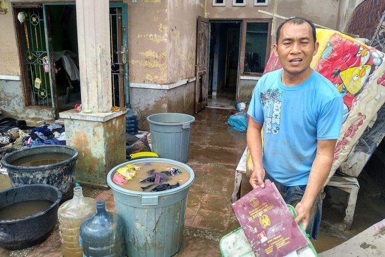 Akuijiduhu Giawa (37) menunjukkan raport sekolah anaknya yang berhasil diselamatkan saat banjir di perumahan De Flamboyan pada Kamis malam hingga Jumat (4/12/2020) dini hari. Dia kehilangan banyak harta benda dan dokumen penting.