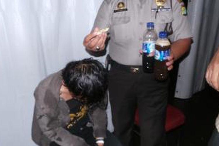 Petugas kepolisian mengamankan seorang penonton konser Slank yang kedapatan membawa ganja dan dua botol minuman keras di Stadion Utama Gelora Bung Karno, Jumat (13/12/2013).