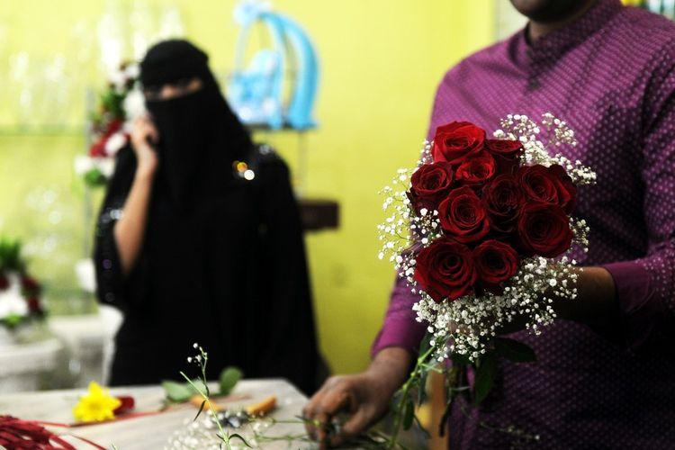 Penjual bunga di tokonya sedang menyiapkan buket pesanan sang klien untuk hari valentine di Jeddah, 14 Februari 2018. (AFP/STRINGER)