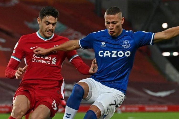 Richarlison menendang bola dibayangi oleh Ozan Kabak dalam laga Liverpool vs Everton pada pekan ke-25 Premier League 2020-2021 yang dilangsungkan di Stadion Anfield, Sabtu (20/2/2021) malam waktu setempat. Foto: PAUL ELLIS/AFP