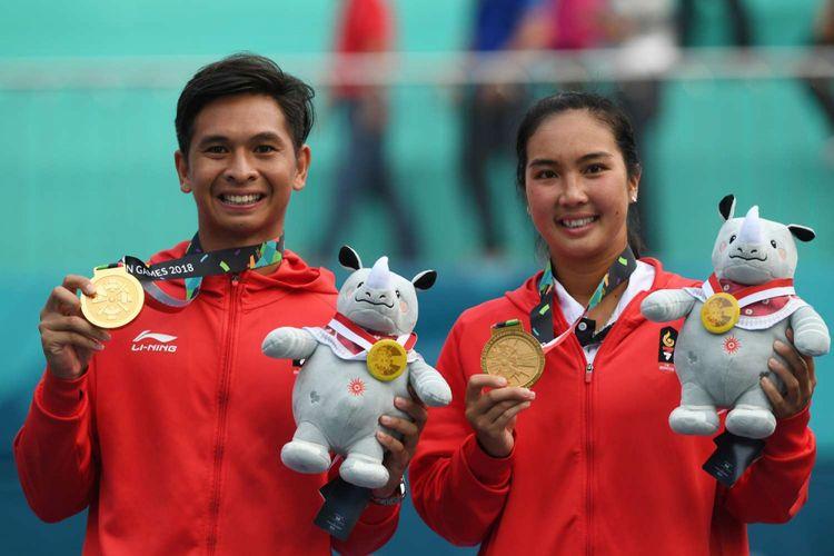 Petenis ganda campuran Indonesia Christopher Rungkat (kiri) dan Aldila Sutjiadi  memperlihatkan medali emas pada upacara penganugerahan medali seusai menang atas petenis Thailand Luksika Kumkhum dan Sonchat Ratiwatana pada final tenis ganda campuran Asian Games 2018 di Jakabaring Sport City, Palembang, Sumatera Selatan, Sabtu (25/8/2018).