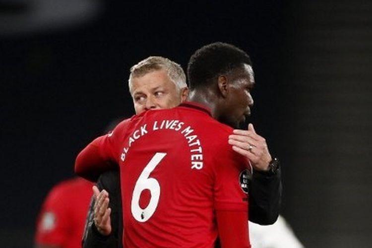 Paul Pogba berpelukan dengan Ole Gunnar Solskjaer usai laga Tottenham Hotspur vs Manchester United pada lanjutan pekan ke-30 Liga Inggris di Tottenham Hotspur Stadium, Sabtu (20/6/2020).