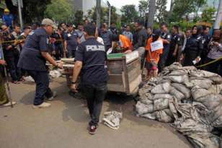 Tersangka menjalani rekonstruksi pencurian kabel di Jalan Medan Merdeka Selatan, Selasa (15/3/2016). Sebanyak enam tersangka melakukan lebih dari 10 adegan saat menjalani rekonstruksi.