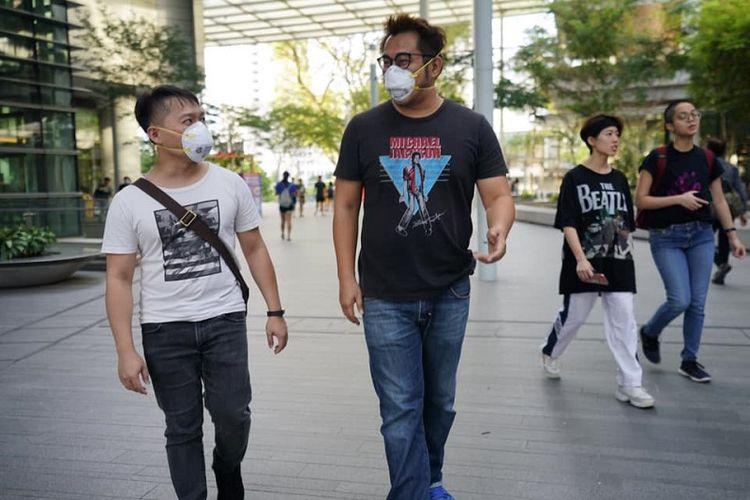 Warga Singapura ada yang terlihat memakai masker dan ada juga yang tidak memakai masker di kawasan University Town, National University of Singapore (NUS), Kamis (30/01/2020)