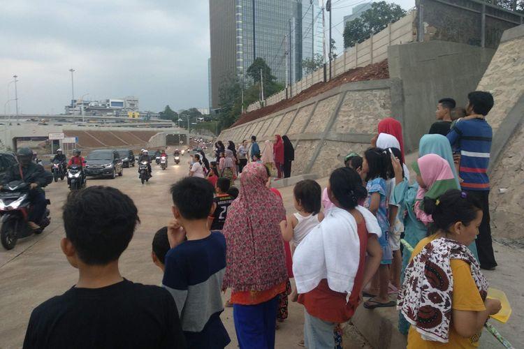 Warga menunggu mobil Presiden Joko Widodo melintas dari peresmian Tol Depok-Antasari, Kamis (27/9/2018).