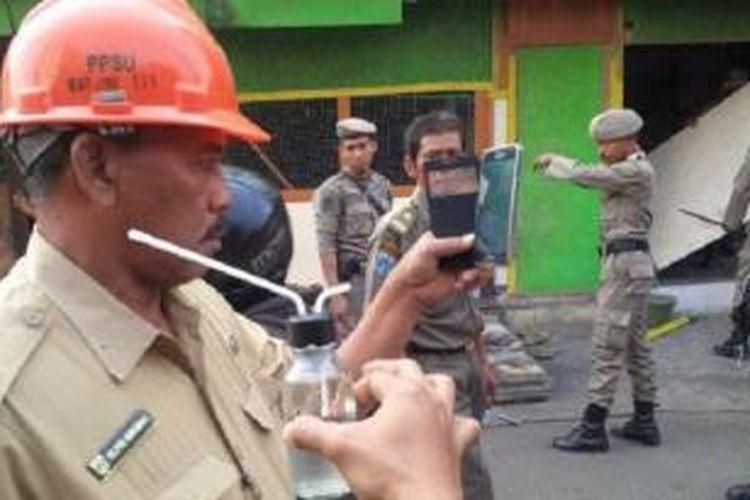 Petugas menunjukkan bong atau alat isap sabu di antara bangunan liar yang dibongkar di Jalan Tanjung Duren Utara, Grogol Petamburan, Jakarta Barat, Selasa (22/9/2015).