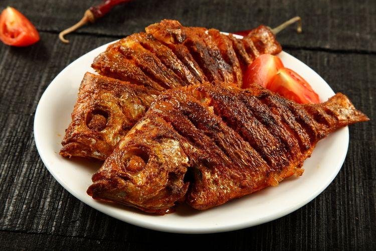 Ilustrasi ikan goreng disajikan di atas piring pada meja kayu.