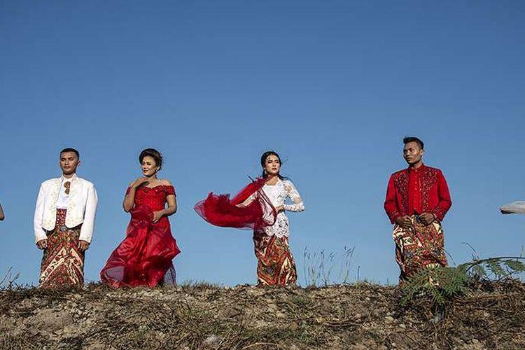 Model mengenakan busana tradisional bertema merah putih saat fashion show di tanggul Lapindo Porong, Sidoarjo, Jawa Timur, Selasa (13/8/2019). Peragaan busana yang menampilkan busana kebaya tersebut untuk memeriahkan HUT ke-74 kemerdekaan RI.