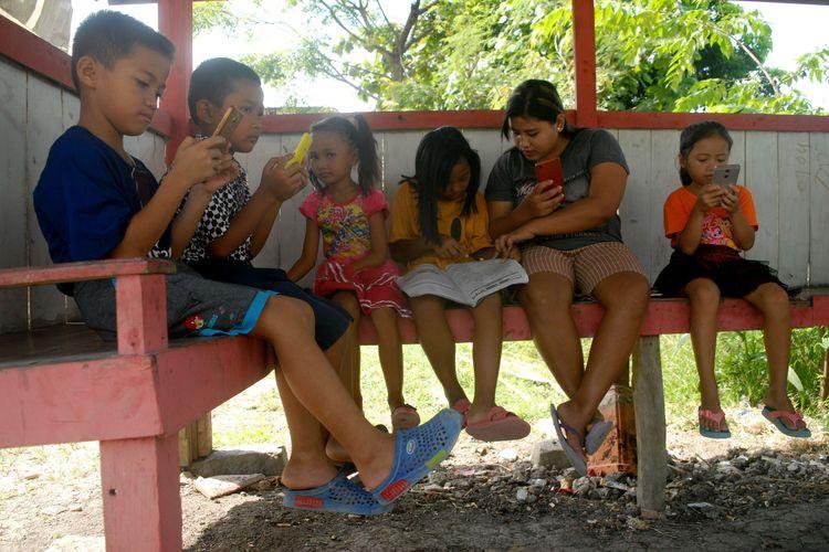 Sejumlah pelajar Sekolah Dasar (SD) ditemani salah seorang wali murid mencari sinyal internet di sebuah gubuk di puncak perbukitan, di Desa Suwatu, Kecamatan Gabus, Kabupaten Grobogan, Jawa Tengah, Selasa (2/6/2020) pagi.