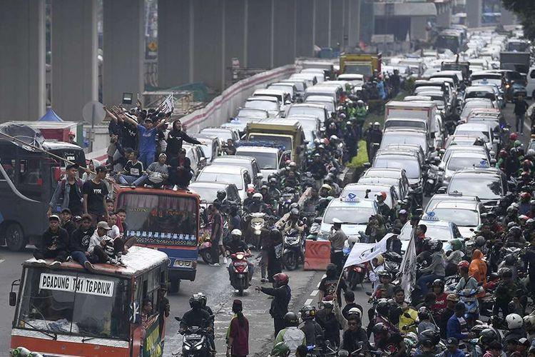 Warga Tanjung Priok menaiki atap metromini saat melakukan aksi di depan gedung Kemenkumham, Jakarta, Rabu (22/1/2020). Ratusan warga Tanjung Priok menuntut Menkumham Yasonna Laoly minta maaf soal ucapan yang menyebut Tanjung Priok merupakan wilayah yang sarat akan tindak kriminal.