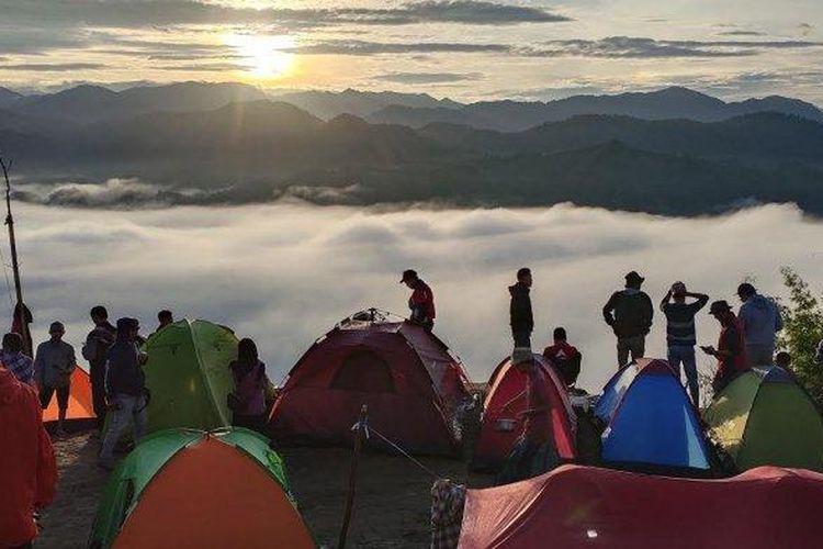 Puluhan wisatawan meniknati indahnya pesona alam Puncak Senayan. Tampak hamparan gulungan awan dan sunrise yang super cantik dari balik barisan gunung Kecamatan Bulo Kabupaten Polman