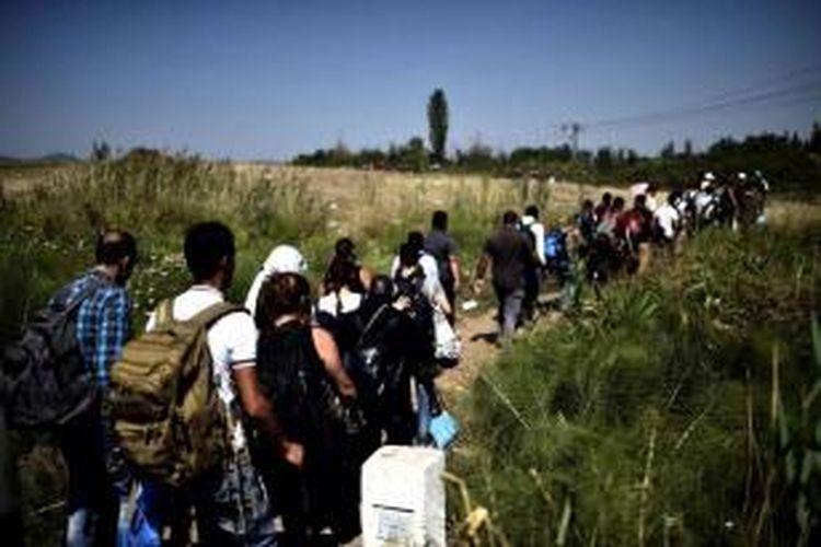 Pengungsi Suriah dan migran berjalan usai melintasi perbatasan antara Macedonia dengan Serbia, 30 Agustus 2015.