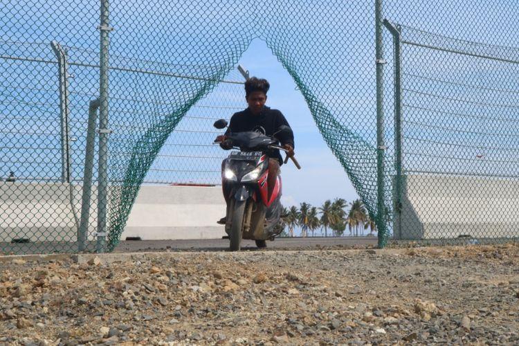 Seorang warga terlihat melintasi pagar Sirkuit MotoGP Mandalika yang dirusak, Jumat (20/8/2021).