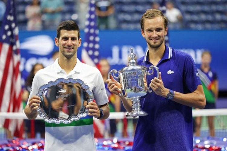 Novak Djokovic (kiri) bersama Daniil Medvedev (kanan) sesuai menyelesaikan final US Open 2021 yang dihelat di di Arthur Ashe Stadium, New York, Amerika Serikat, pada Senin (13/9/2021) pagi WIB.