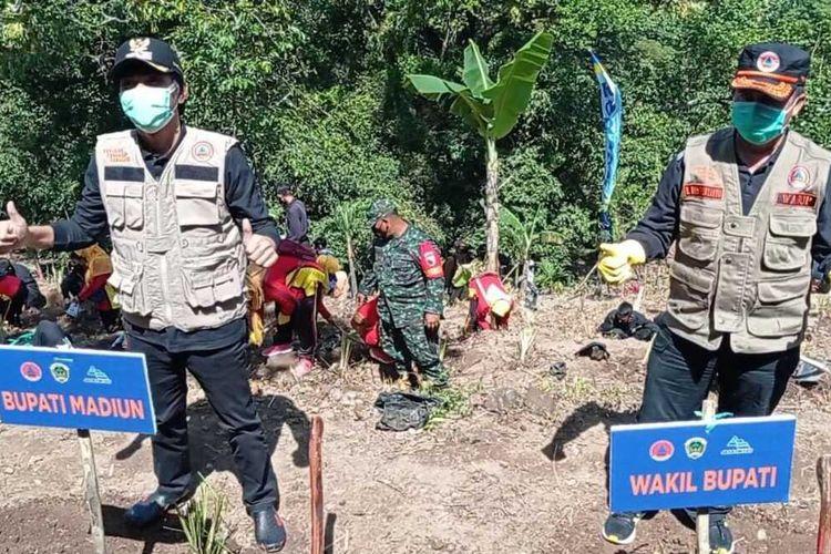 TANAM—Bupati Madiun, Ahmad Dawami (kiri) menanam 10.000 akar wangi di daerah rawan bencana longsor saat memperingati hari air sedunia di Desa Cermo, Kecamatan Kare, Kabupaten Madiun, Jawa Timur, Senin (22/3/2021).