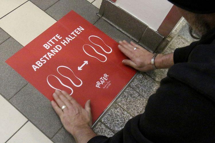 Seorang pegawai restoran di Wina, Austria pada Kamis (14/5/2020) menempatkan tanda jarak yang ditempel di lantai dan berbunyi, tolong jaga jarak Anda.