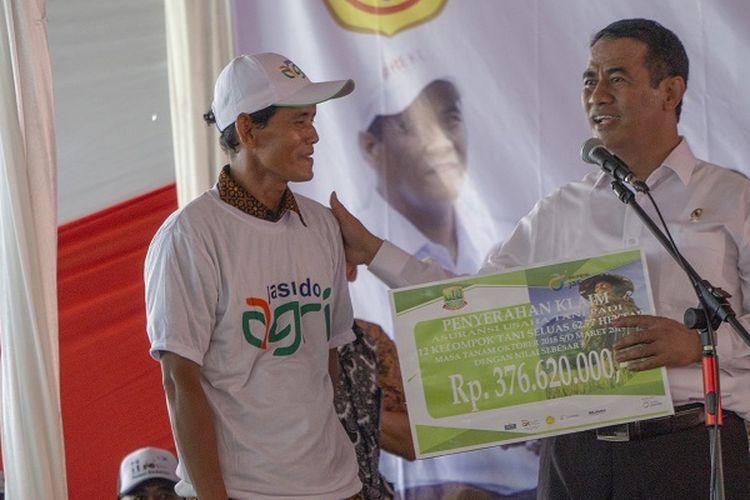 Menteri Pertanian Andi Amran Sulaiman secara simbolis memberikan bantuan alsintan dan asuransi pertanian kepada petani di Lapangan Sepak Bola Panji Larang, Desa Pacing Kecamatan Jatisari, Kabiupaten Karawang, Selasa (26/3/2019).