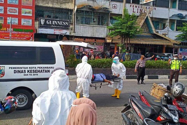 Petugas Puskesmas dengan mengenakan APD mengevakuasi seorang kakek yang pingsan di Pasar Cik Puan, Pekanbaru, Kamis (21/5/2020). Dok. Istimewa.