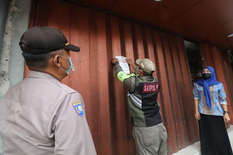 Petugas memasang stiker himbauan menutup tempat usaha non esensial saat razia di Jalan Doho, Kota Kediri, Jawa Timur, Jumat (16/7/2021). Razia di pusat pertokoan tersebut guna memastikan penerapan  Pemberlakuan Pembatasan Kegiatan Masyarakat (PPKM) Darurat berjalan dengan baik guna memutus mata rantai penyebaran COVID-19. ANTARA FOTO/Prasetia Fauzani/foc.
