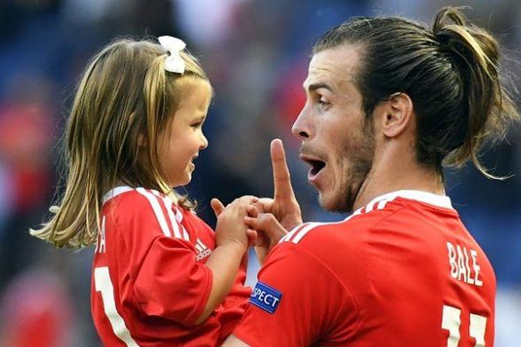 Pemain Wales, Gareth Bale, menggendong anak perempuannya, Alba Violet, usai laga kontra Irlandia Utara di Paris, pada 25 Juni 2016.