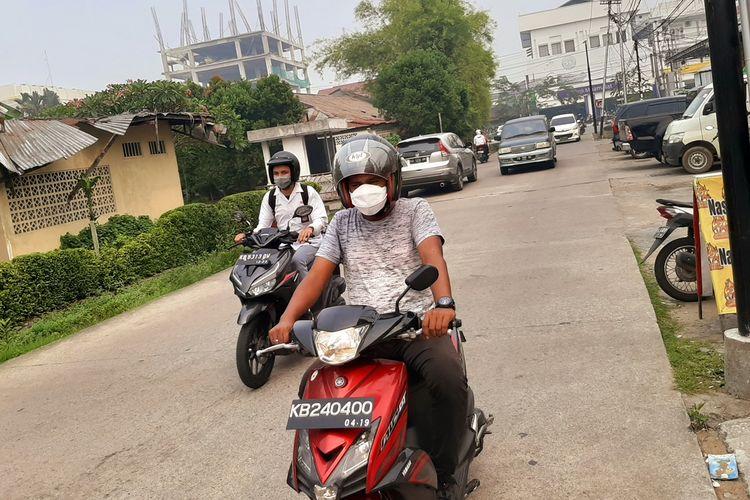 Seorang warga mengenakan masker sewaktu melintas di Jalan Putri Daranante, Kota Pontianak, Kalimantan Barat, Senin (16/9/2019). Berdasarkan data Dinas Kesehatan Kalbar, tercatat 6.026 penderita ISPA sejak terjadinya bencana karhutla.
