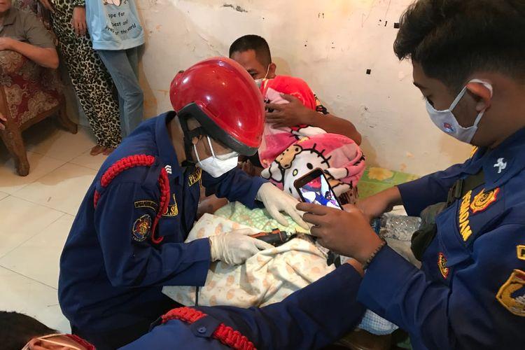 Anggota Suku Dinas Penanggulangan Kebakaran dan Penyelamatan Jakarta Selatan melakukan pemotongan cincin di tangan Ratna yang bengkak akibat luka bakar pada Senin (22/12/2020) sore.