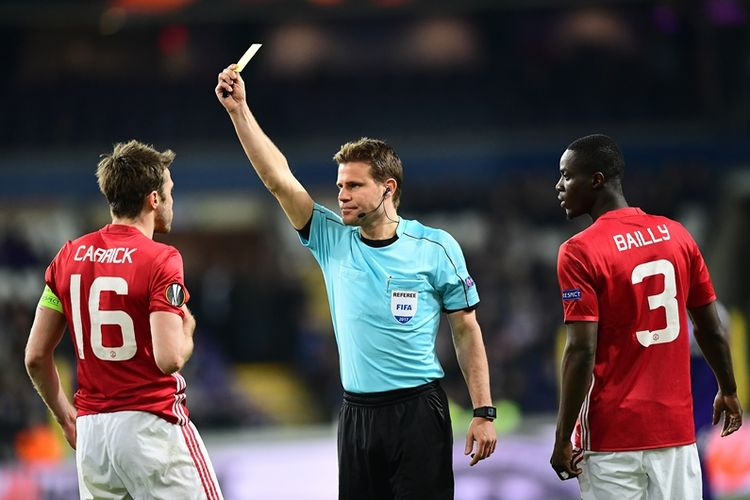 Wasit asal Jerman, Felix Brych (tengah), memberikan kartu kuning kepada gelandang Manchester United, Michael Carrick (kiri), yang disaksikan bek Manchester United, Eric Bailly, dalam pertandingan leg pertama babak perempat final Liga Europa melawan Anderlecht di Stadion Constant Vanden Stock, Brussels, 13 April 2017.