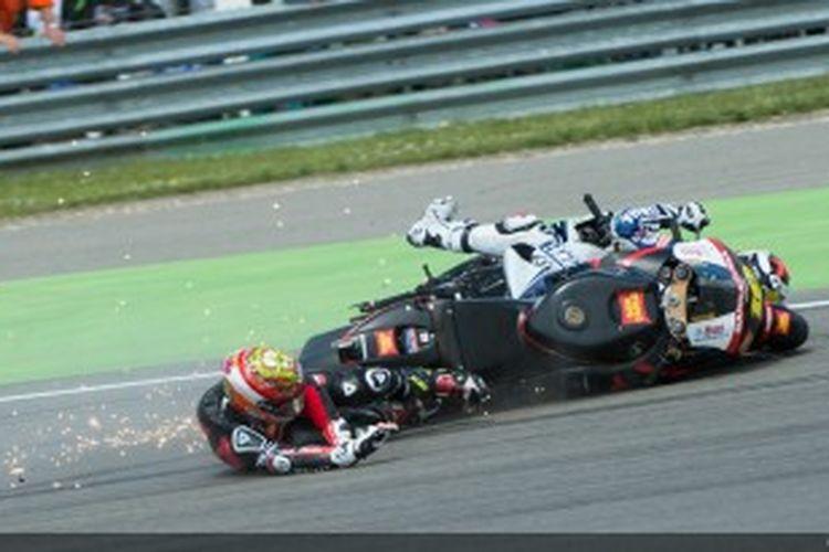 Pebalap Honda, Alvaro Bautista terjatuh dan mengenai Jorge Lorenzo di tikungan pertama sirkuit Assen pada balapan GP Belanda, 30 Juni 2012.