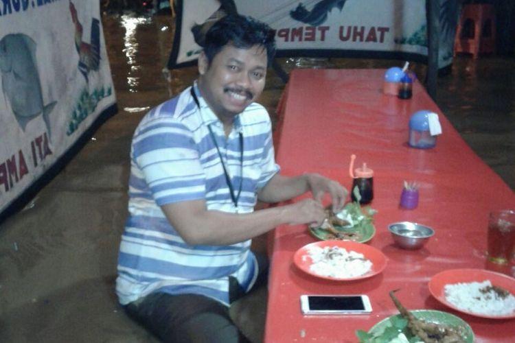 Ahmad Saiful Bahri atau Ipunk makan di tengah banjir Jatinegara, Jakarta.